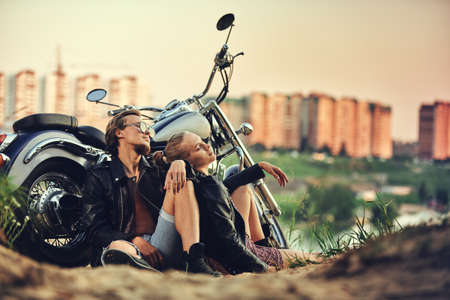 Young beautiful couple hipsters in stylish clothing for a retro motorcycle on the street, outdoor portrait, posing, in jeans and t-shirts, bearded guy, blonde girl, travel together 스톡 콘텐츠