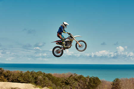 Extreme concept, challenge yourself. Extreme jump on a motorcycle on a background of blue sky with clouds. Copy space, all or nothing.