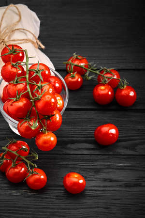 Fresh organic cherry tomatoes on a dark background, food delivery. Copy space 스톡 콘텐츠