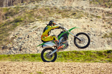 Motocross driver in action accelerating the motorbike takes off and jumps on springboard on the race track. 스톡 콘텐츠