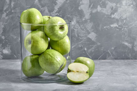 green apples on the table. Top view with copy space on gray stone background.
