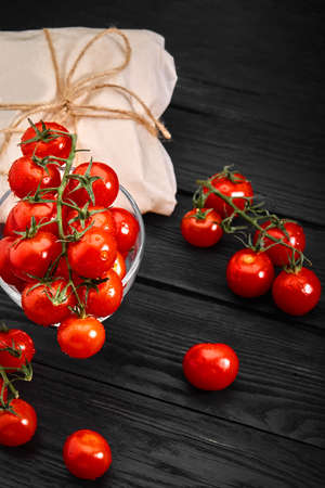 Fresh organic cherry tomatoes on a dark background, food delivery. Copy space. 스톡 콘텐츠