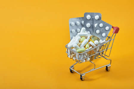 Mini shopping cart, pills and capsules on yellow background. Online drugstore. Pharmaceutical industry. Epidemic, painkillers, healthcare and treatment concept. Flat lay. copy space. Imagens