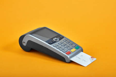 Payment by credit card. Terminal on yellow background copy space