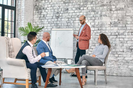 Confident businessman writing on flip charts presentation new project in boardroom at company meeting. Serious mentor auditor speaks with partners about business using board and graphs.