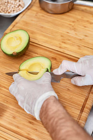 Professional chef cutting avocado on table in kitchen, closeup