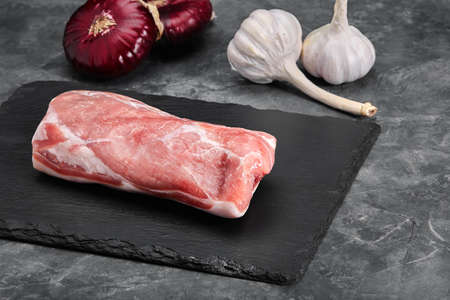 Fresh tenderloin with rosemary, raw meat, top view, on a stone background.