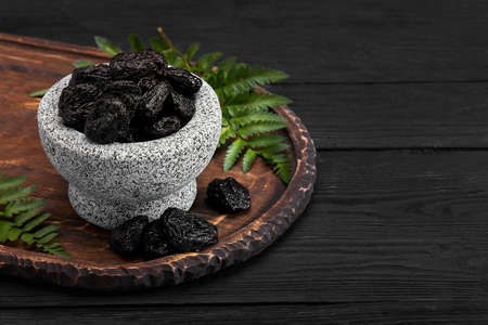 Fresh prunes in stone bowl. Prunes on stone dark table. Prunes healthy food. Dried plums in bowl.