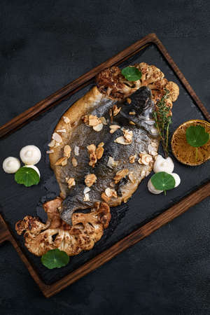 Fish dishes cooking preparation with dorado in backing form in shape of fish with healthy vegetables on dark rustic background with ingredients, top view. Seafood concept. 免版税图像