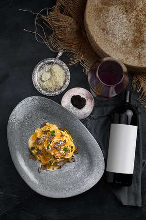 Italian cuisine - spaghetti with black truffle on a gray plate and bottle of wine. Selective focus. Vertical.