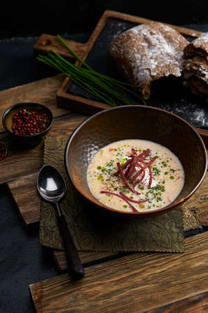 Traditional Italian soup with barley and bresaola on old wooden background. Selective focus. Dark tone.