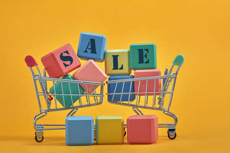 A miniature shopping cart and multi-colored cubes on yellow background. Sales word written on cubes.