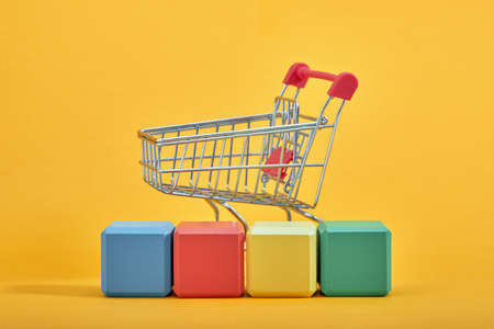A miniature shopping cart and wooden blocks with the wordings SALE, isolated against mint background. Archivio Fotografico