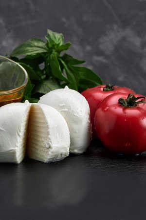 Tomato, basil leaves, mozzarella cheese balls on gray background. Italian Caprese salad ingredients.