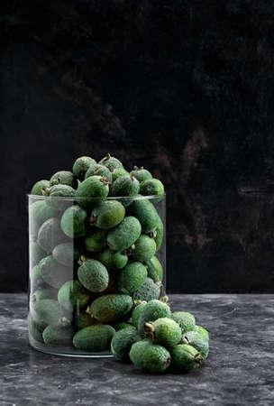 green feijoa fruit in glass vase on a black background