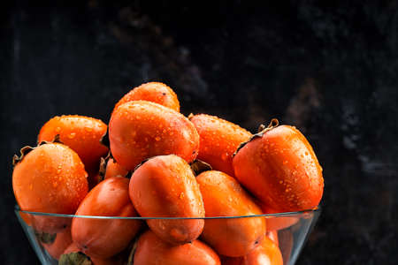 Delicious raw ripe persimmon fruit on dark rusty metal background copy space