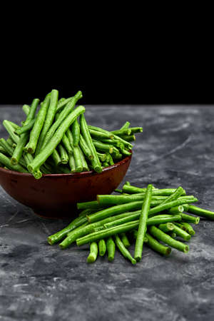 Washed raw green beans stalks in a bowl on dark background. Superfood for healthy life concept