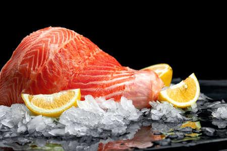 Fresh raw salmon fish steak on ice over dark stone background. Creative layout made of fish, top view, flat lay