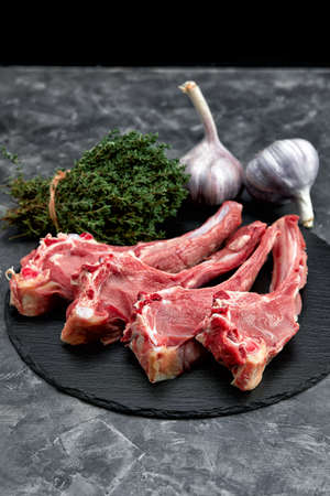 Raw cowboy steak. Marbled beef meat with spices on a stone background