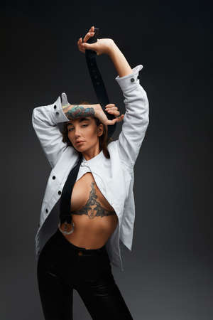 Portrait of sexy young woman undressing on grey background. Female model taking her shirt off.