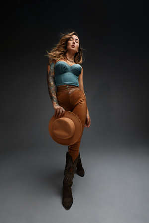 Fashion portrait of young brunette girl in blue western top and jeans with cowboy hat and boots in front of gray copy space studio background. Fashion portrait and lifestyle. Archivio Fotografico