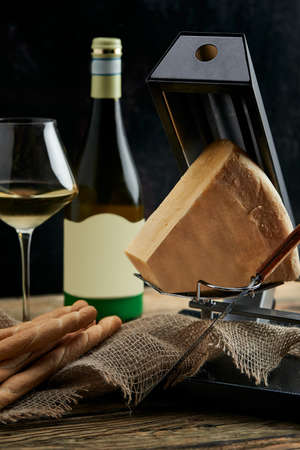 cheese as a perfect gourmet appetizer to a glass of white wine: bread sticks, parmesan served on a wooden board, on a black background Archivio Fotografico