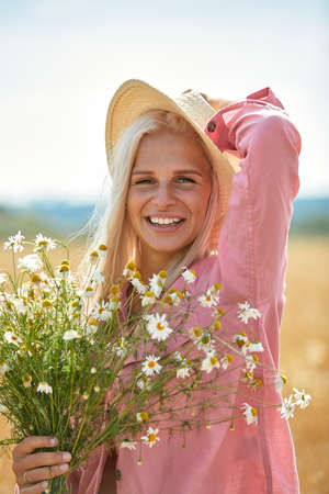 Beautiful woman in hat and with a basket of field daisies in sunny summer day. Archivio Fotografico