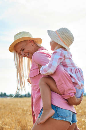 happy mother holding baby smiling on a wheat field in sunlight Archivio Fotografico