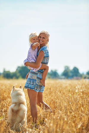 Cute baby girl with mom and dog on wheat field. Happy young family enjoy time together at the nature. Mom, little baby girl and dog husky resting outdoors. togetherness, love, happiness concept. Archivio Fotografico