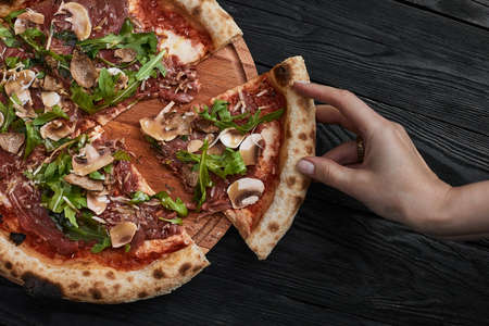 Close up on delicious freshly baked small pizza with melted cheese mushrooms and arugula