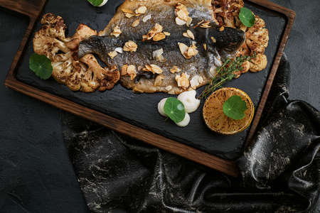 Fish dishes cooking preparation with dorado in backing form in shape of fish with healthy vegetables on dark rustic background with ingredients, top view. Seafood concept. Archivio Fotografico