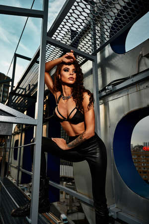 sexy brunette woman with a beautiful figure posing on the rooftop against the backdrop of a big city Archivio Fotografico