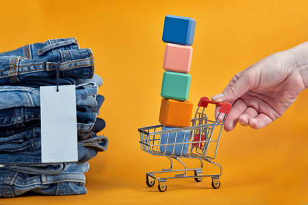 A stack of blue jeans with a white blank tag on a yellow background. Shopping trolley with multi-colored cubes. Sales consept 免版税图像