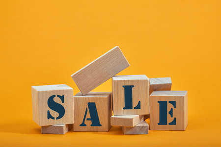 wooden blocks with the wordings SALE, isolated against yellow background.