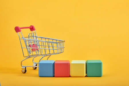 empty wooden cubes mockup style, copy space with shopping trolleys on yellow background. Colourful blocks template for creative design, place for text 免版税图像