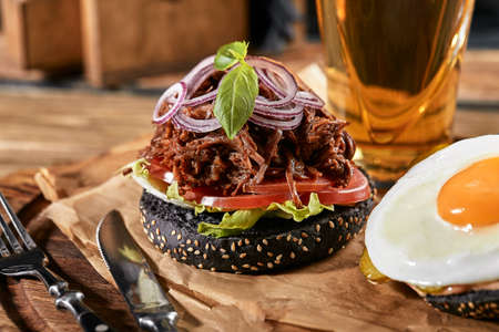 Good Burger, with beef, onions, sweet onions, cheese, lettuce, tomato on craft paper with glass of beer on the background 免版税图像