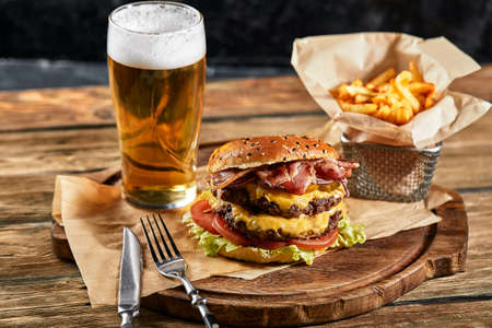 A large mouth-watering burger with grilled beef patty and fresh vegetables. Tasty american cheeseburger on a wooden board. Classic homemade burger in craft paper.