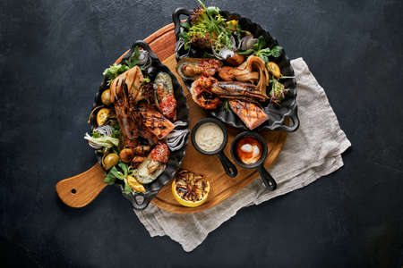 Mixed Roasted Seafood Platter Set. Contain Grilled Big Shrimps, Calamari Squids and Barracuda Fish Garlic Pepper with Spicy Chili Sauce and Potatoes, on wooden board and Black Background.