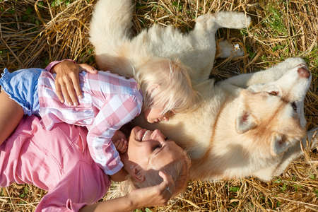 Cute baby girl with mom and dog on wheat field. Happy young family enjoy time together at the nature. Mom, little baby girl and dog husky resting outdoors. togetherness, love, happiness concept. 免版税图像