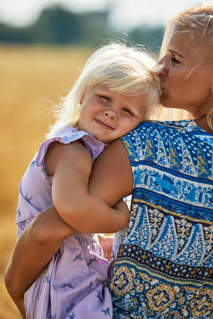 happy mother holding baby smiling on a wheat field in sunlight 免版税图像
