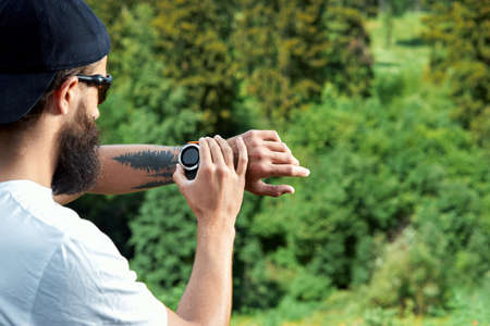 Healthy smart lifestyle concept. Muscular athlete doing great exercising outside in sunny park. Young handsome man in sportswear checking sport tracker watch.