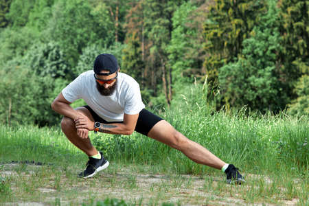 Bearded athletic man doing workout exercise in the outdoor gym in sunset 免版税图像