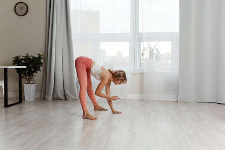 Fitness home. Beautiful woman doing some exercises at home in a living room.