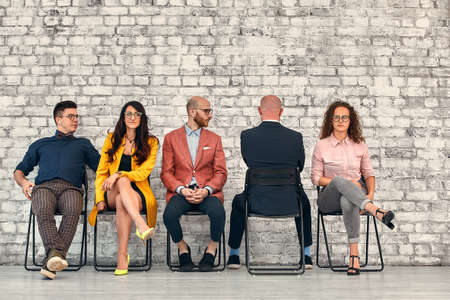 Corporate employees. Business matters discussion. Solid team ignoring lonely colleague. Foto de archivo