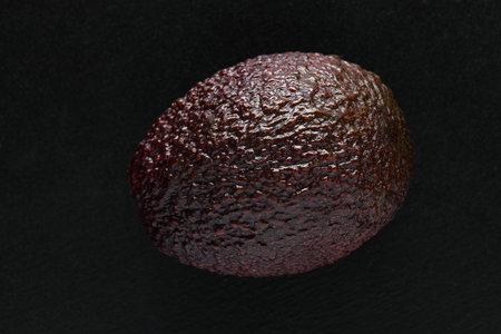 Single red hass avocado on a black background. Close-up macro studio shot. Zdjęcie Seryjne