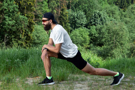 Bearded athletic man doing workout exercise in the outdoor gym in sunset Standard-Bild