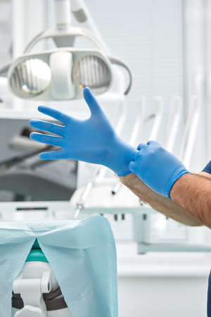 A female dentist puts on gloves against a background of dental equipment in a dental office. Happy patient and dentist concept.