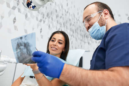 people, medicine, stomatology and health care concept - happy male dentist showing work plan to woman patient at dental clinic office Standard-Bild