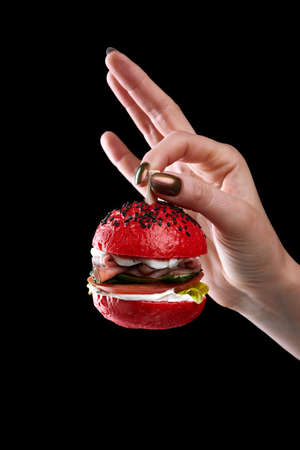 female hand holding mini burger as a Christmas tree toy on black background Standard-Bild