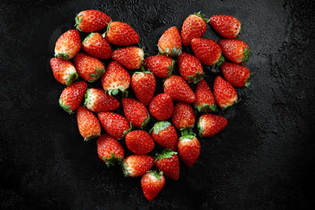 Fresh strawberries array heart shape on black background. Love concept. Valentines Day Concept. Winter Concept. Standard-Bild